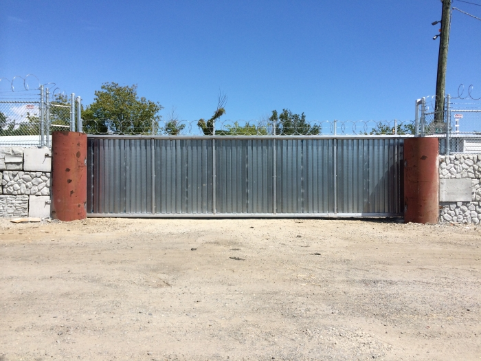 Solid Steel Security Gate with Corrugated Metal and Razor Ribbon